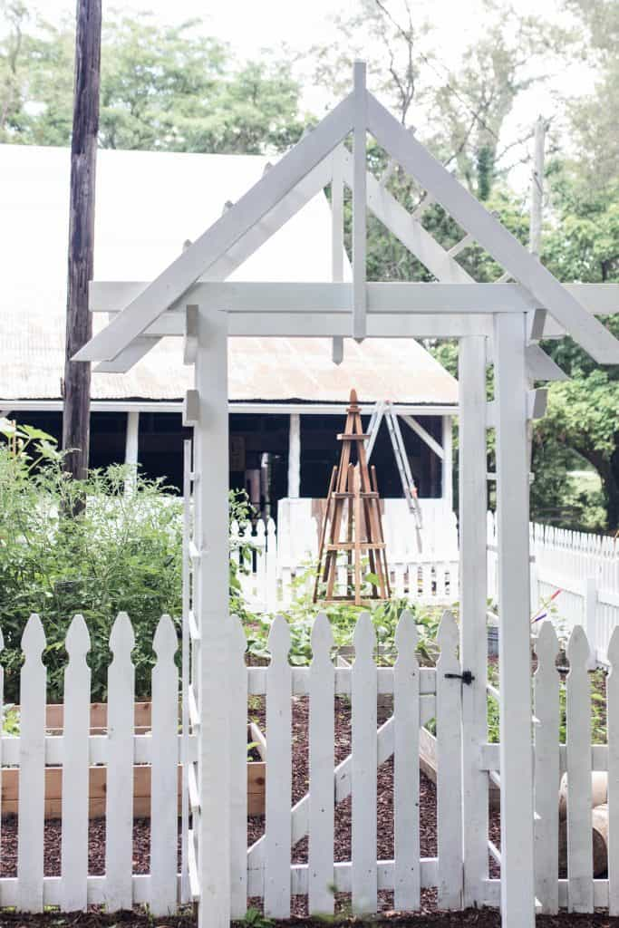 white arbor with a white picket fence into a garden