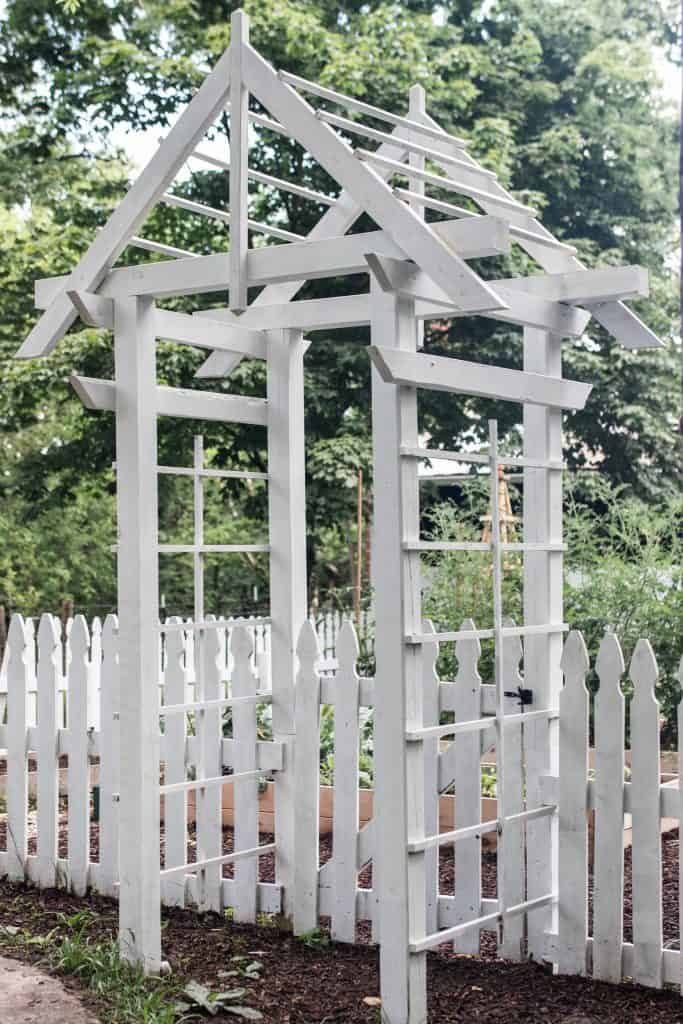 side view of a white arbor against a white picket fence with trees in the background