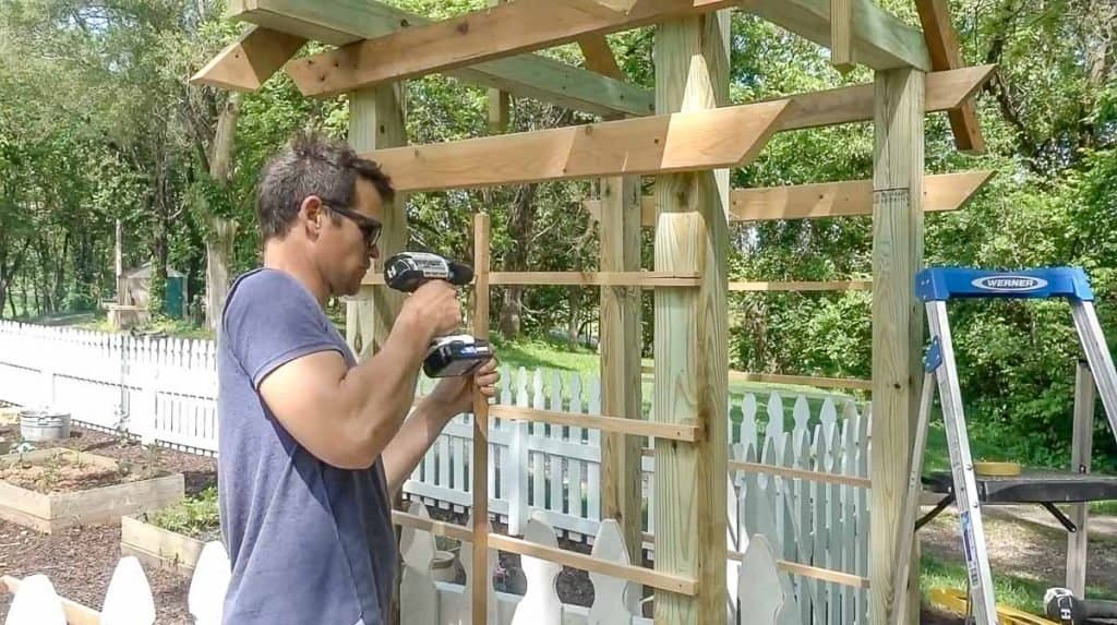 man drilling in a center post to lattice on a arbor