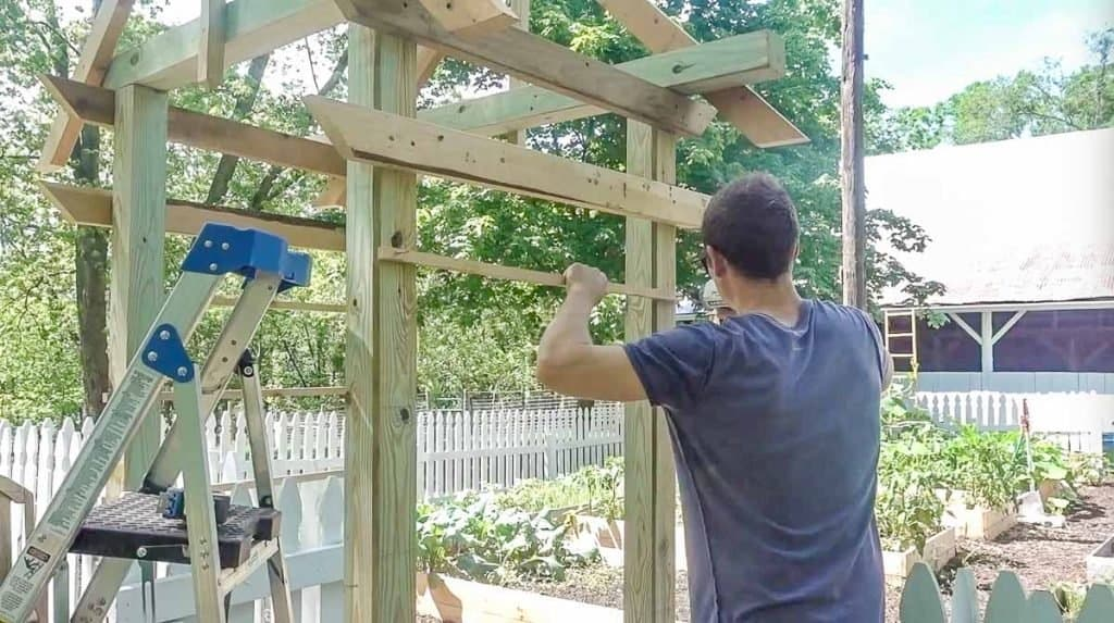 man acting cross strips of wood on an arbor as a trellis