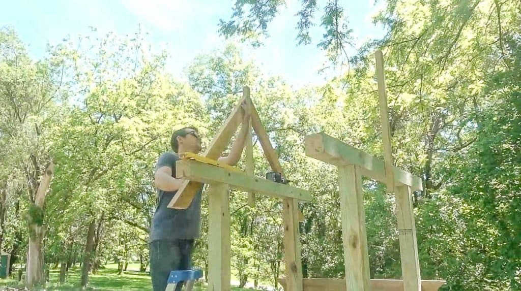 man drilling arbor roof pitch into center post