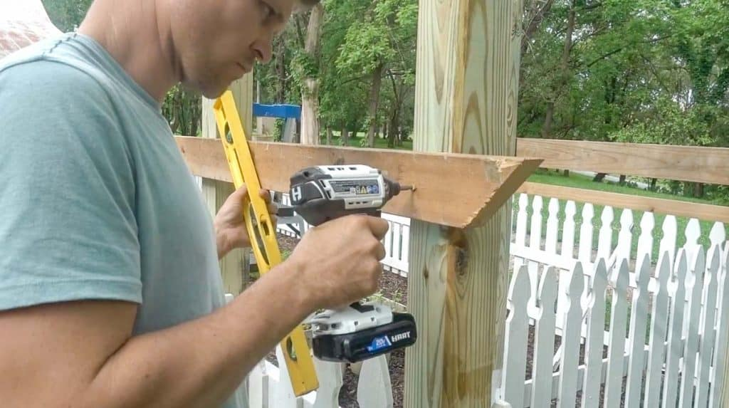 man screwing in a 2x4 into arbor posts