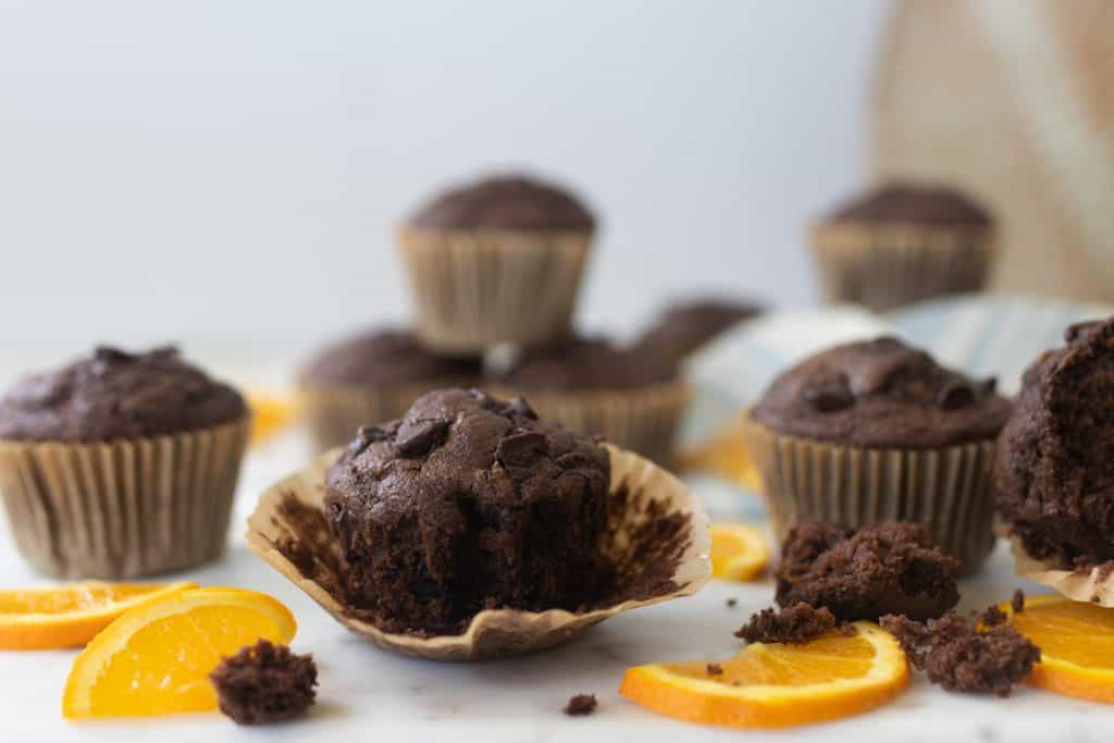 sourdough chocolate zucchini muffins on a countertop with sliced oranges