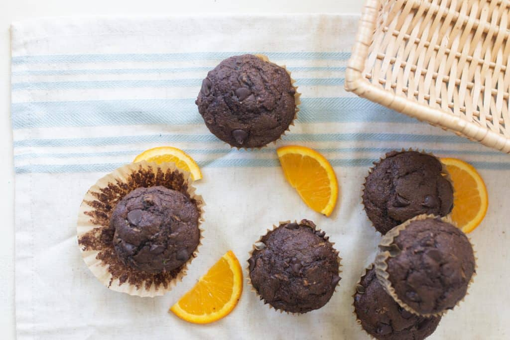 overhead photo of zucchini chocolate muffins on a blue and white stripped table cloth with orange slices spread about the muffins