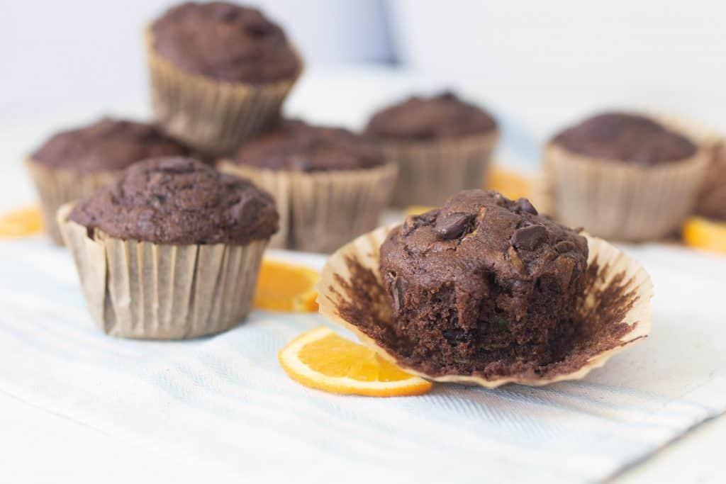 chocolate zucchini muffins placed on a white countertop with orange slices around the muffins