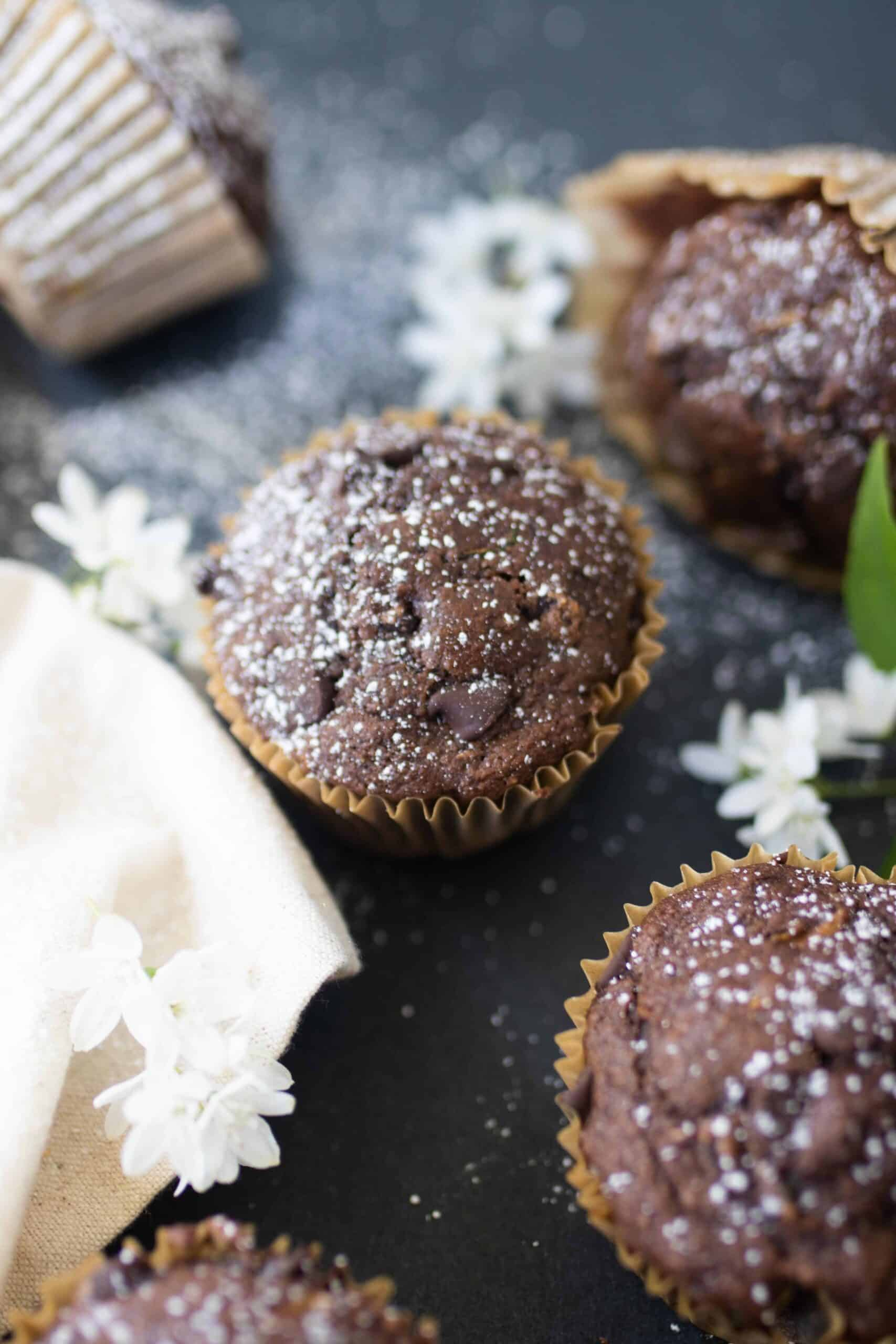 sourdough chocolate zucchini muffins spread out on a black countertop with white flowers and a white napkin on the countertop