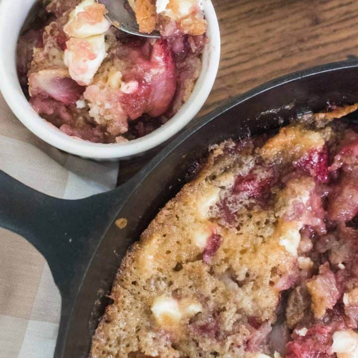 sourdough strawberry cream cheese cobbler in a cast iron skillet with a portion in an antique cup with a spoon in the back