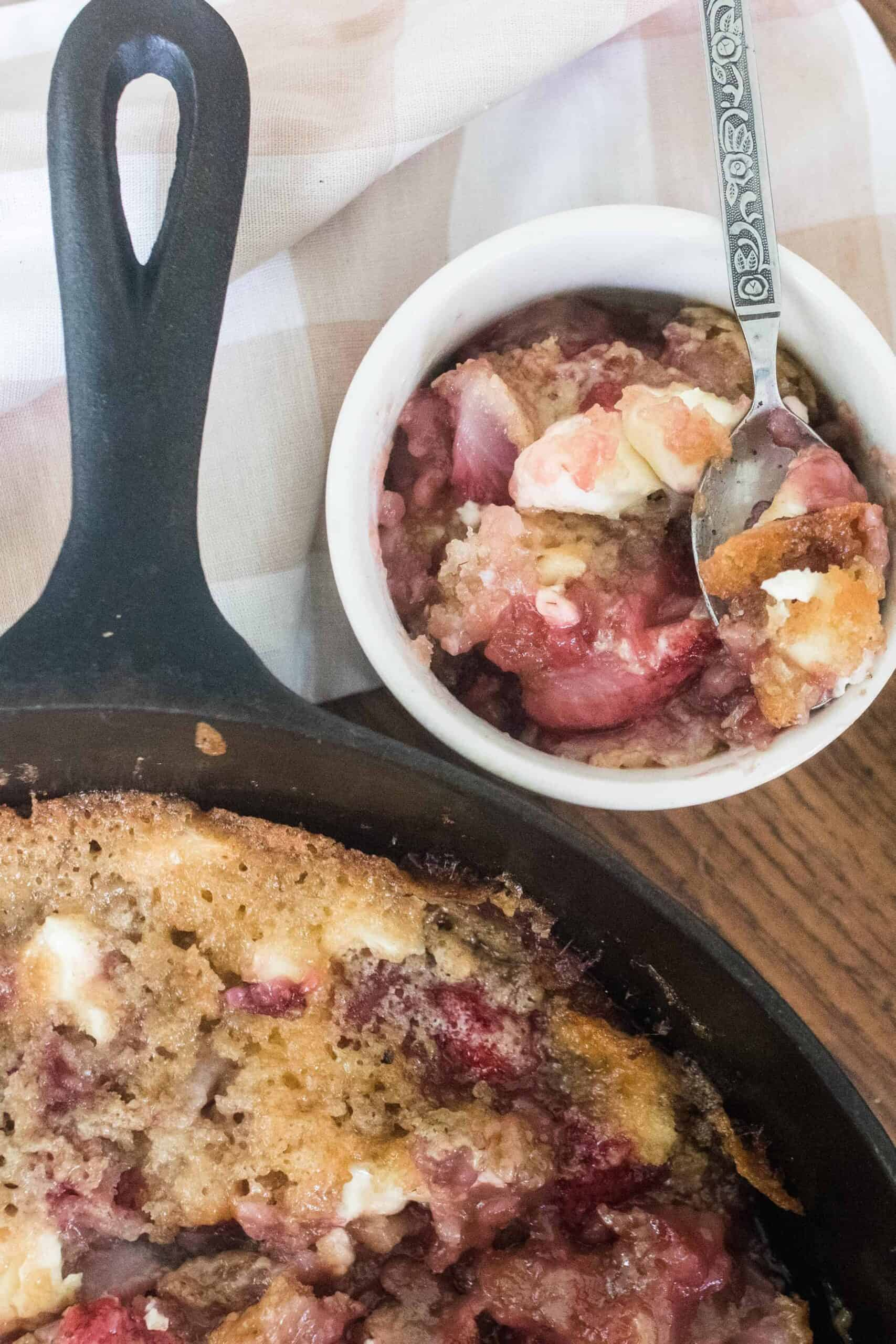sourdough strawberries and cream in a cast iron skillet with a white ramekin of cobbler with a fork behind it