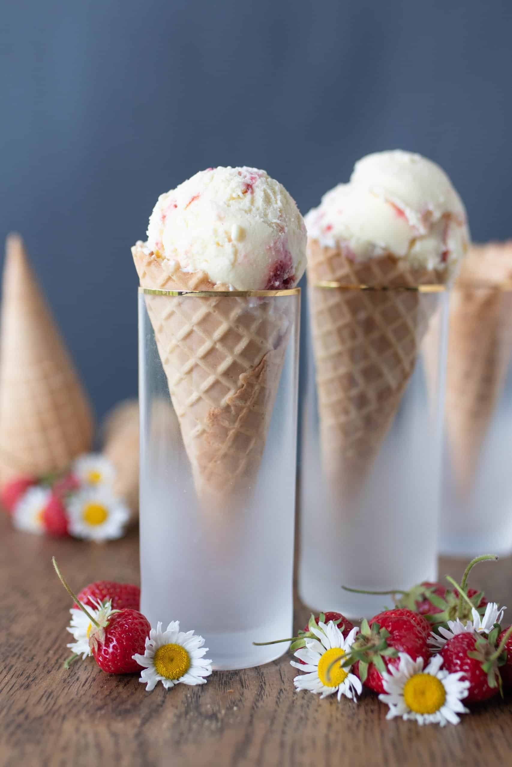 cones filled with strawberry cheesecake ice cream in cones in glasses on a wood table with strawberries and flowers spread across the table