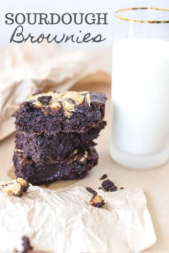 three sourdough brownies stacked up on parchment paper with a glass of milk to the right