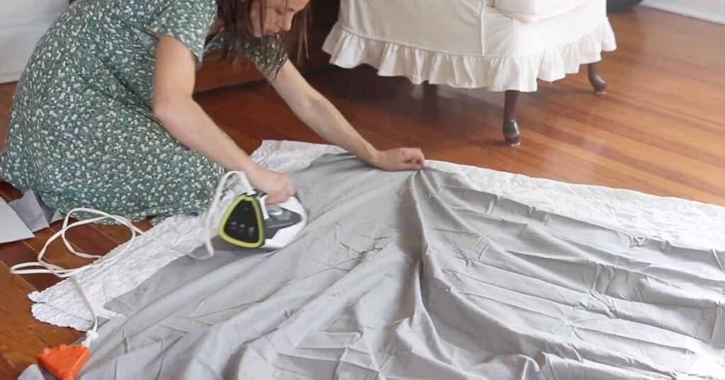 women ironing fabric on the floor