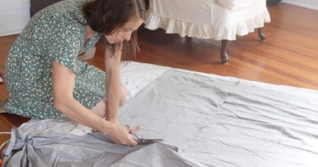 women cutting a sheet to create the top piece of a bed skirt