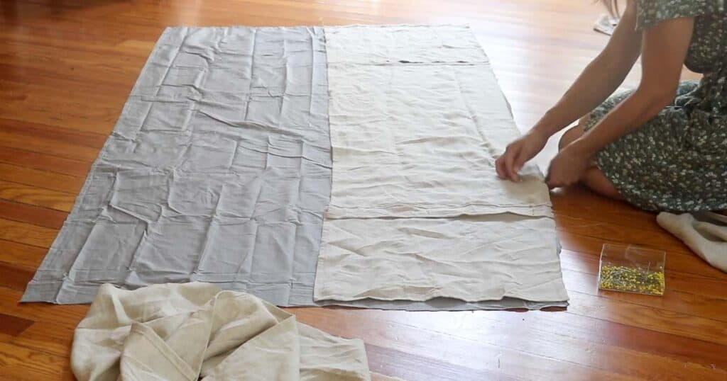 women sitting on the floor pinning a bed skirt panels to the top sheet