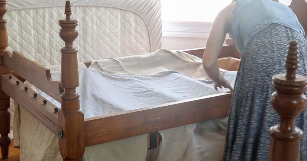 women placing a DIY beds skirt onto a antique bed to make sure it fits
