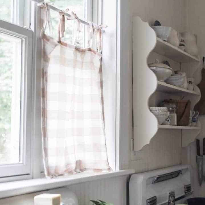 peach and cream linen DIY cafe curtain handing on a kitchen window above an antique farm sink