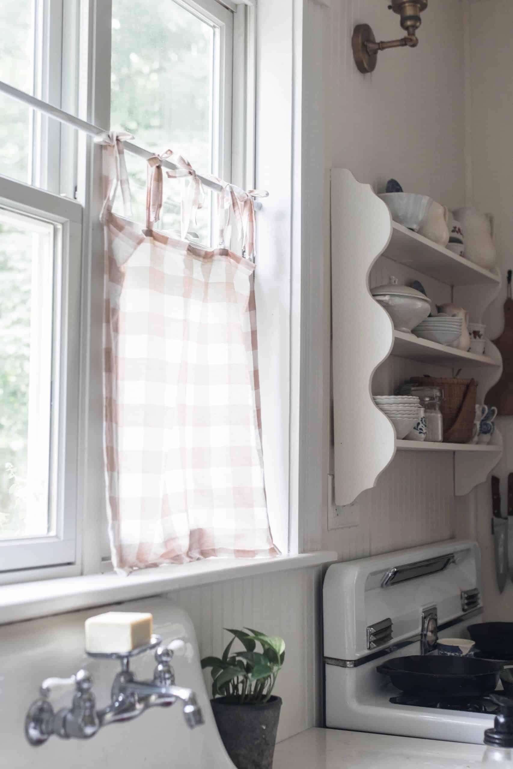 peach and cream linen DIY cafe curtain handing on a kitchen window above an antique farm sink