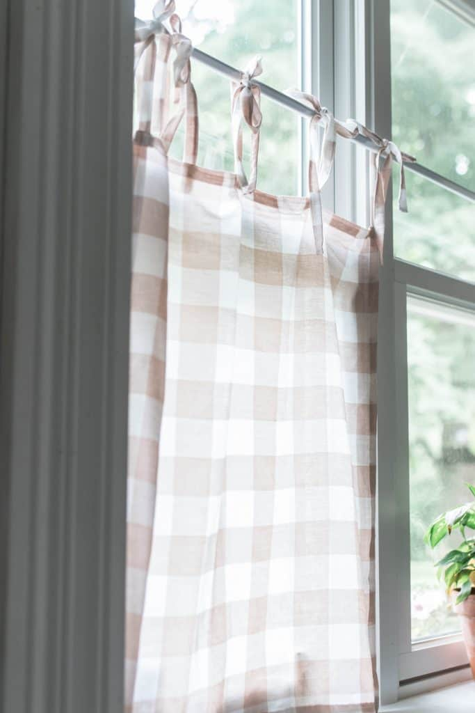 diy cafe curtains peach and white buffalo check hanging on a tension rod in a kitchen window
