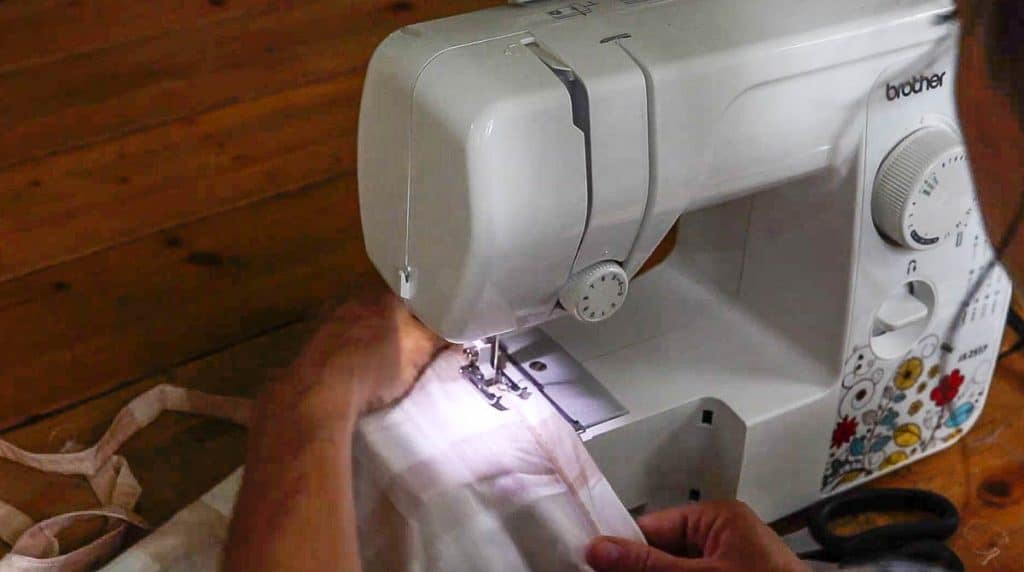 hem being sew into fabric to create curtains