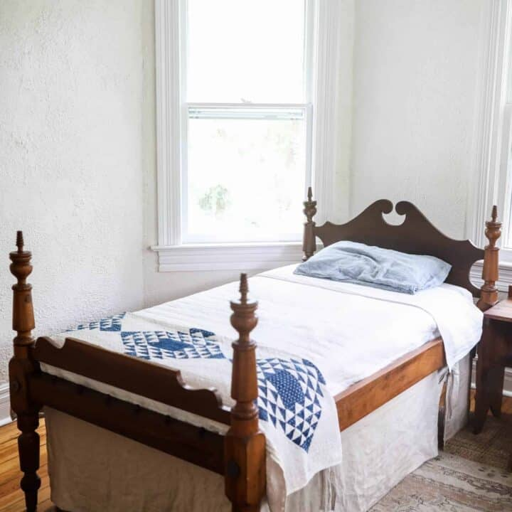 antique wooden bed with a white bedspread, blue and white build near the footboard and a linen bed skirt