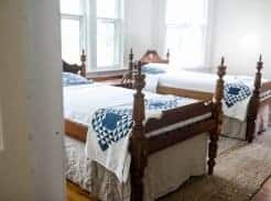 two antique wood beds with diy bed skirts made from linen