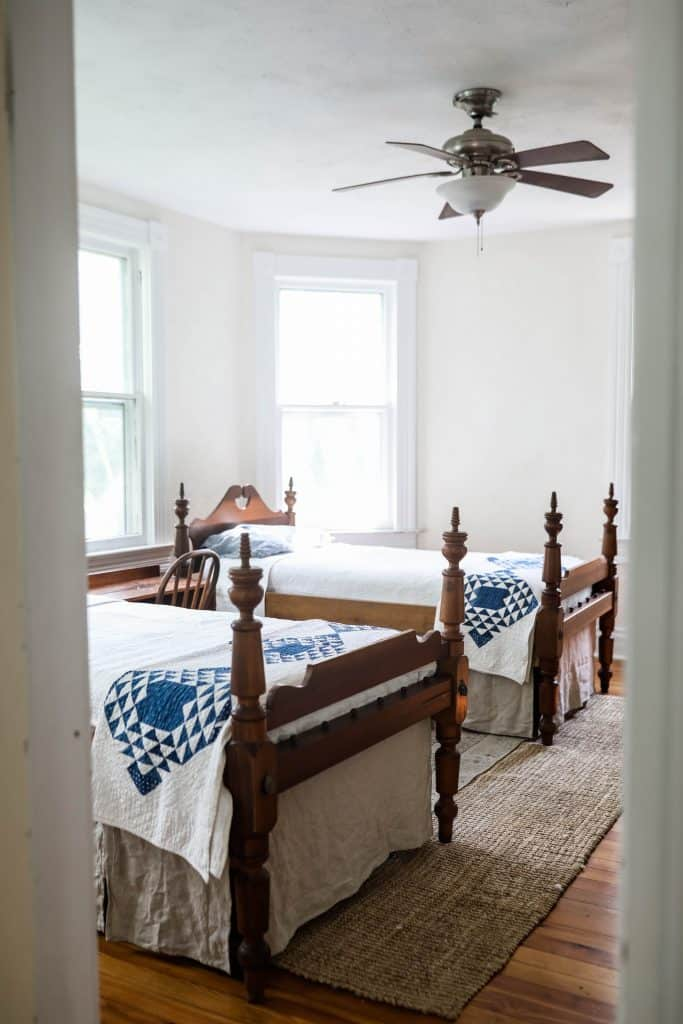 two antique wooden beds with linen bed skirts and blue and white quilts near the end of the bed