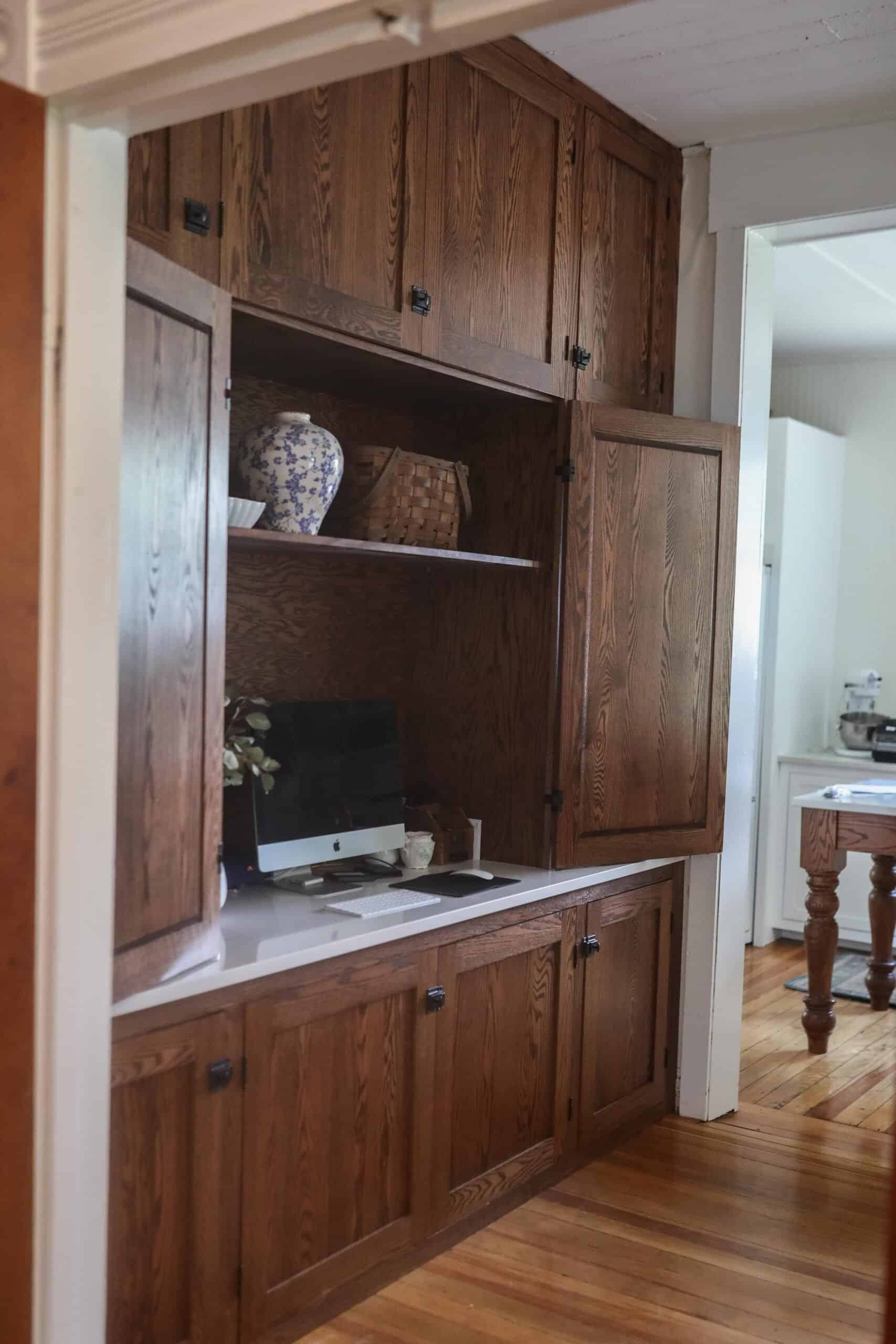 wood cabinet doors open to reveal an organized office