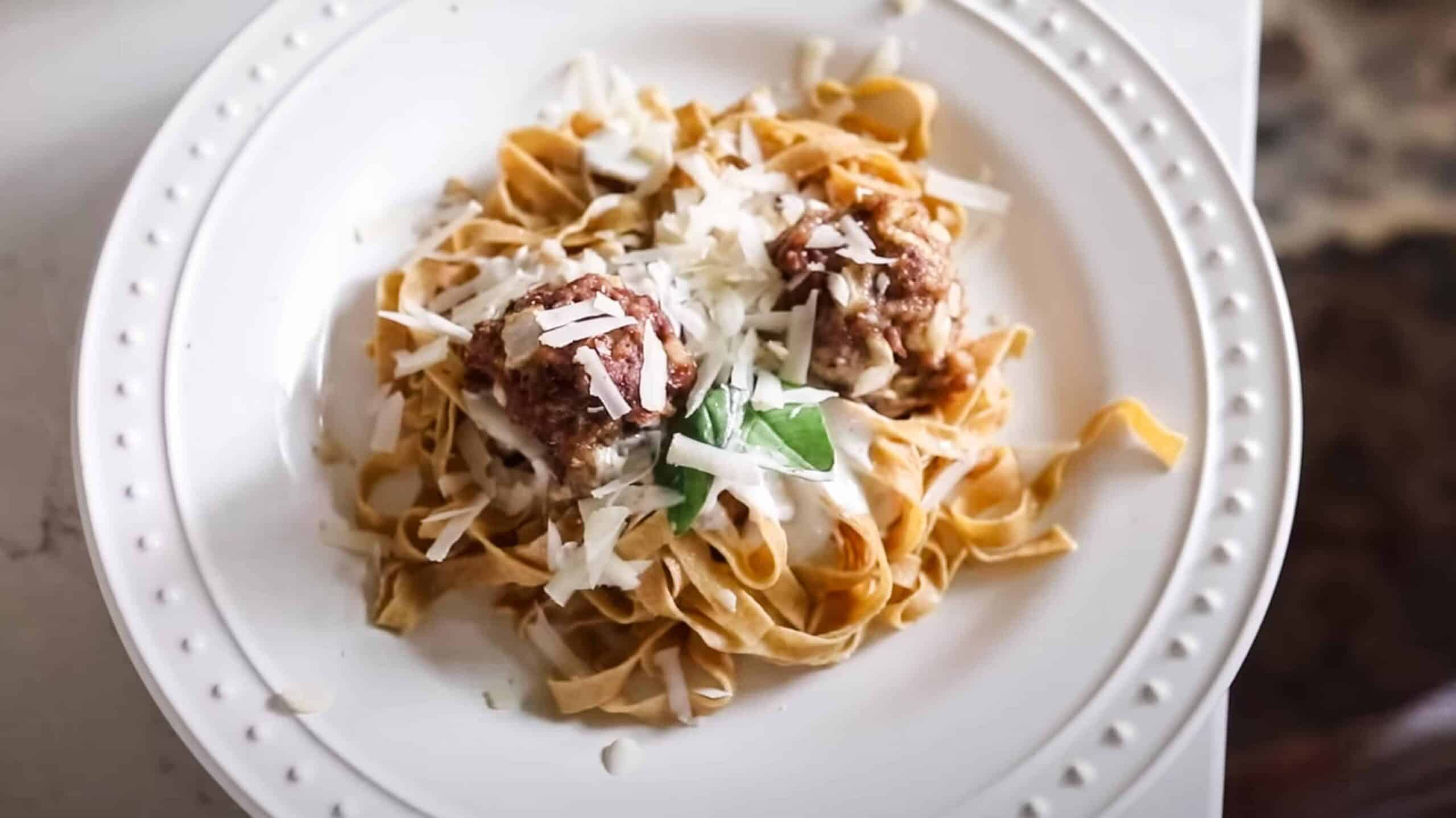 fresh homemade einkorn pasta on a white plate and topped with meatballs fresh herbs and cheese