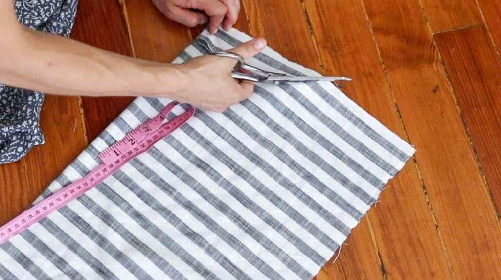women cutting stripped fabric to create a neckline for a shirt
