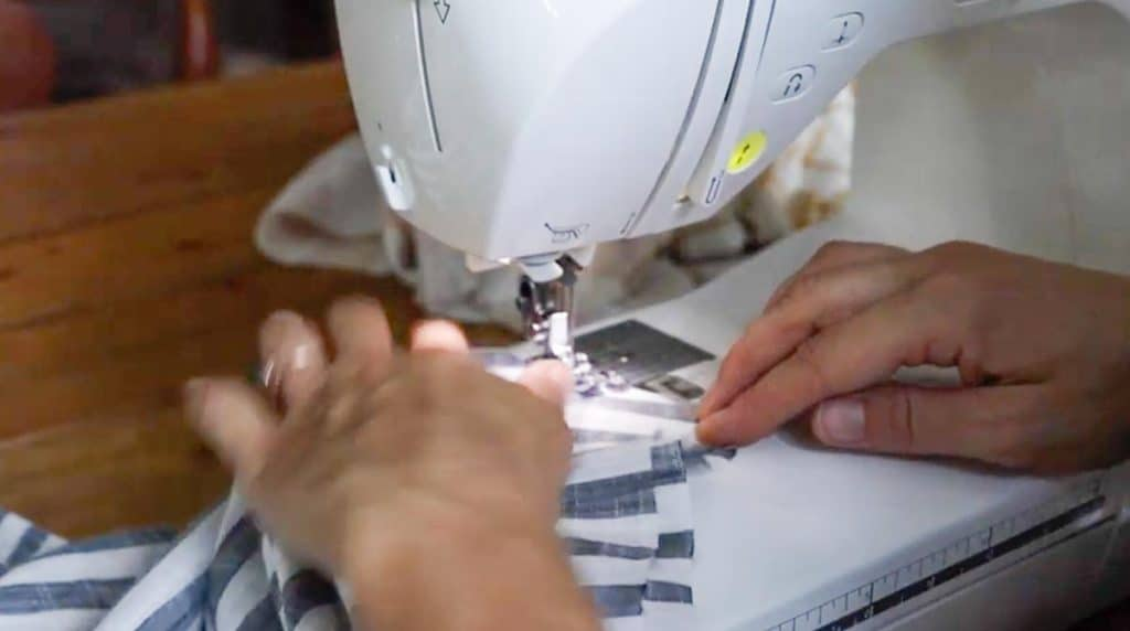 women using sewing machine to sew sleeve onto main body piece