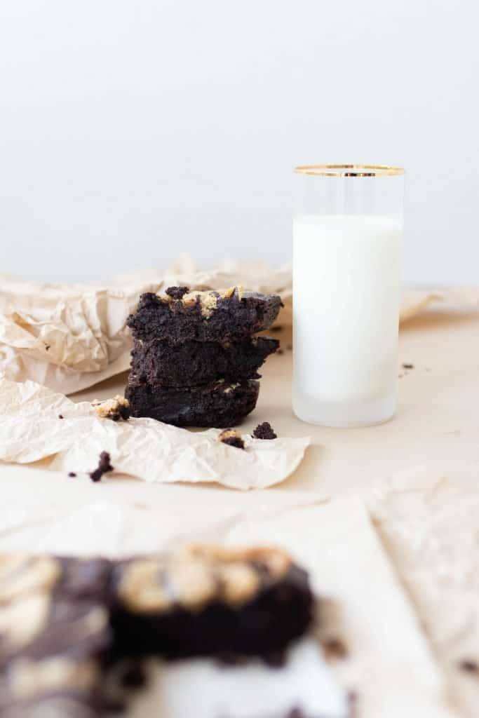 sourdough brownies on parchment paper with more brownies and a glass of milk in the background