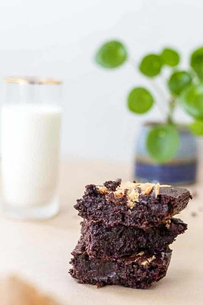 3 sourdough brownies stacked up on parchment paper. A glass of milk and a green plant in a blue vase in the background