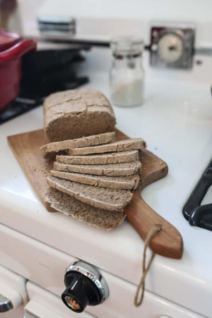 loaf of sourdough rye bread on a wood cutting board on an antique stove