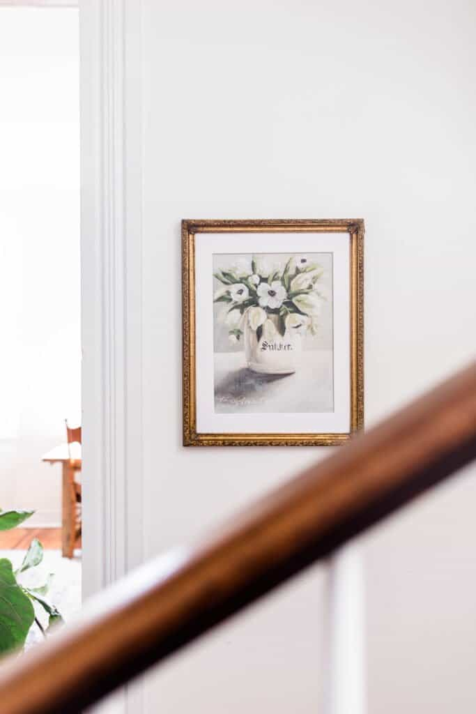 farmhouse floral print in a gold frame on a white wall