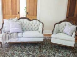 a victorian loveseat and chair freshly painted with chalk paint in a soft green color on a rug with pillows and a blanket draped over