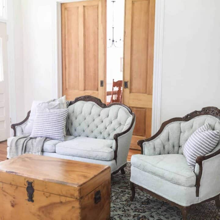 victorian couches painted a soft green in a living room with a wood chest as a coffee table