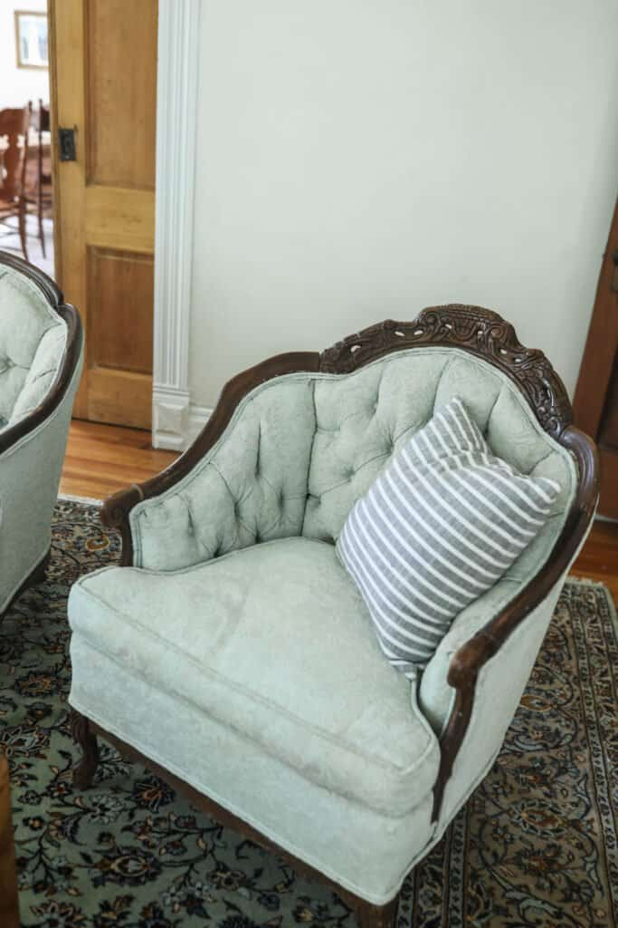 victorian love seat with a stripped pillow