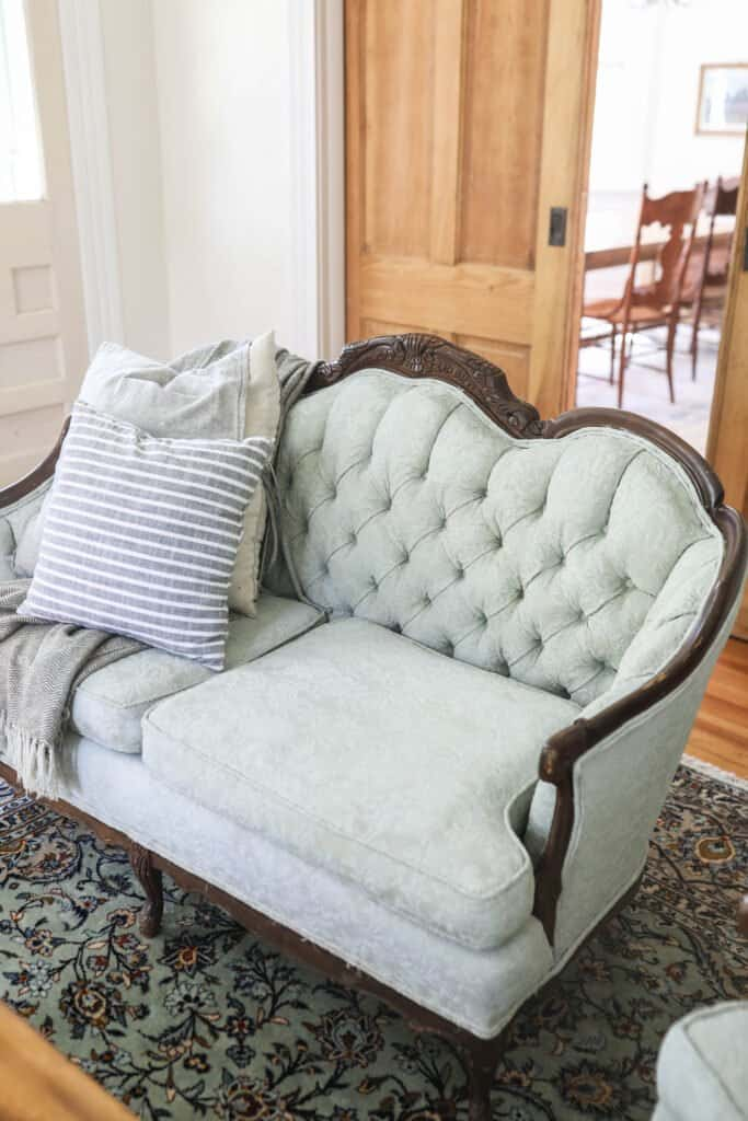 victorian loveseat chalk painted soft green in a living room with pillows