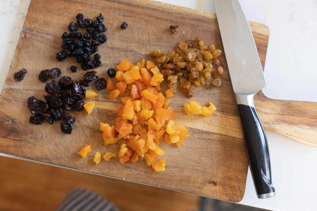dried fruit on a cutting board being chopped with a knife