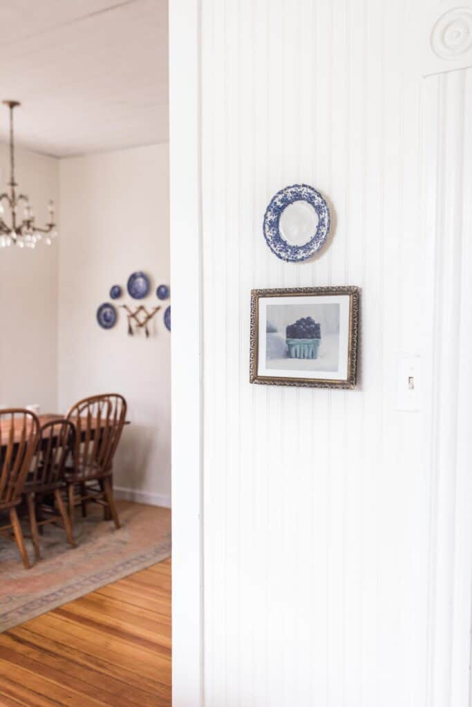 blueberry print in a antique frame with a blue and white plate hanging above it