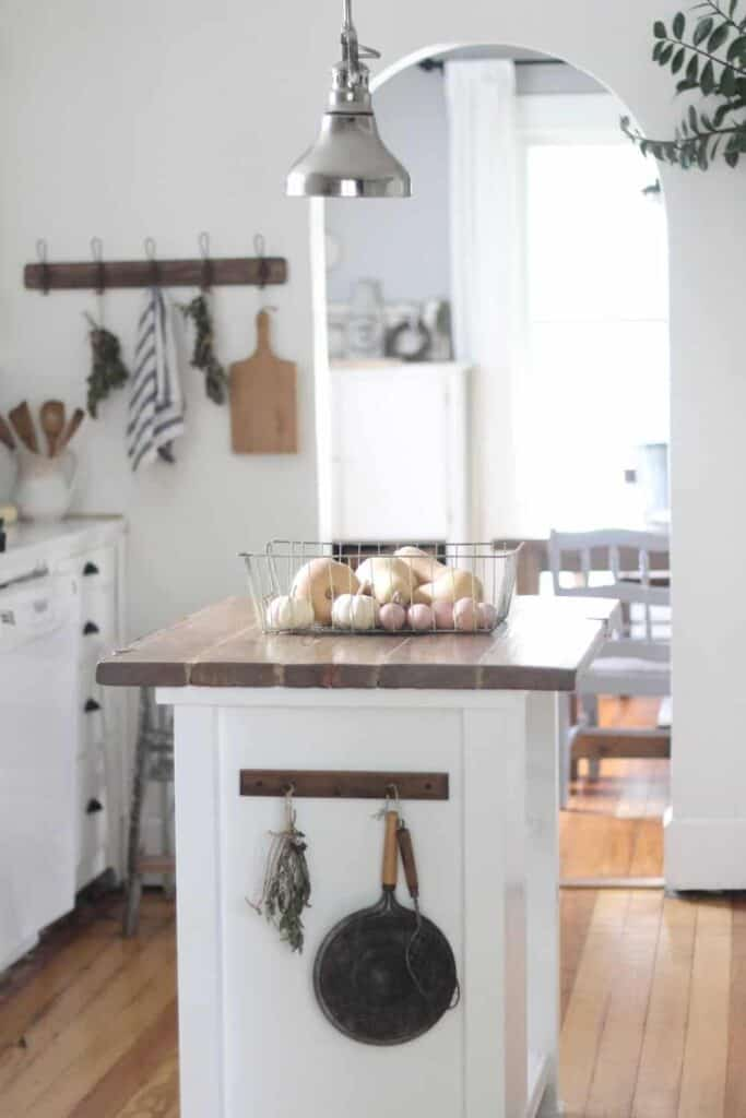 apron and cutting boards hanging on a kitchen wall