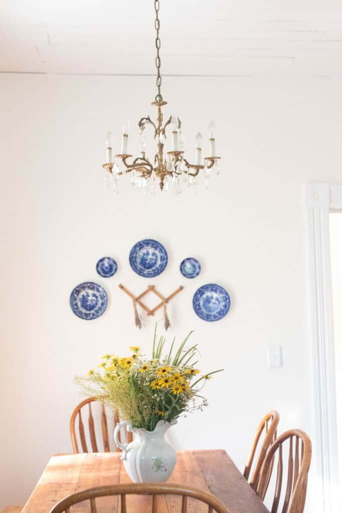 blue and white antique plates hanging on a wall above a farmhouse table