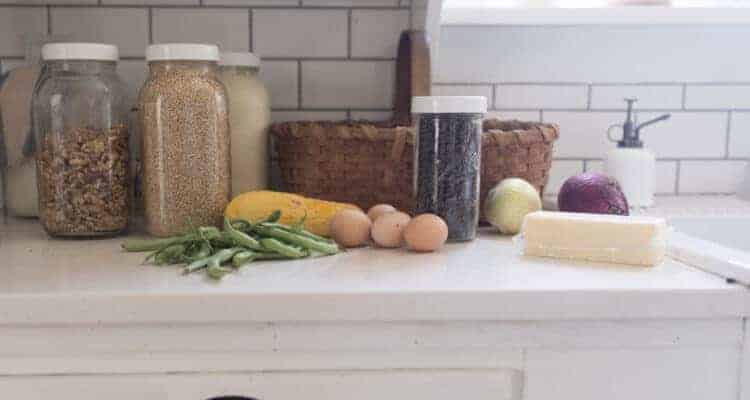dry goods from azure standard stored in jars on a kitchen countertop  with eggs, butter, and veggeies.