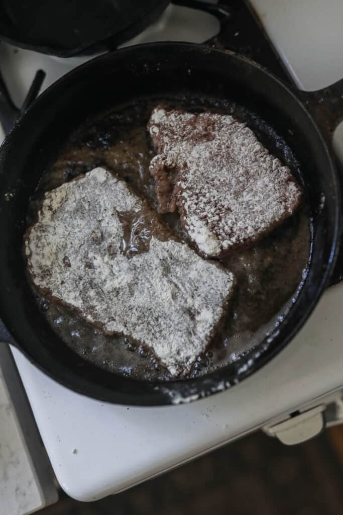 round steak dredged in flour and browning in a cast iron skillet with coconut oil
