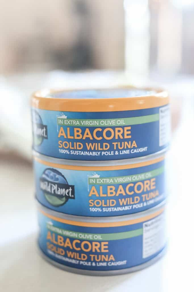 3 cans of Wild Planet Tuna stacked up on a white countertop