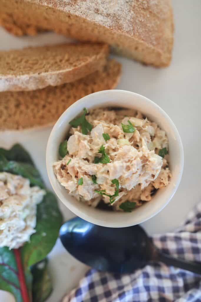 tuna salad in a white bowl with bread behind it. A spoonful of tuna salad on a leaf of lettuce