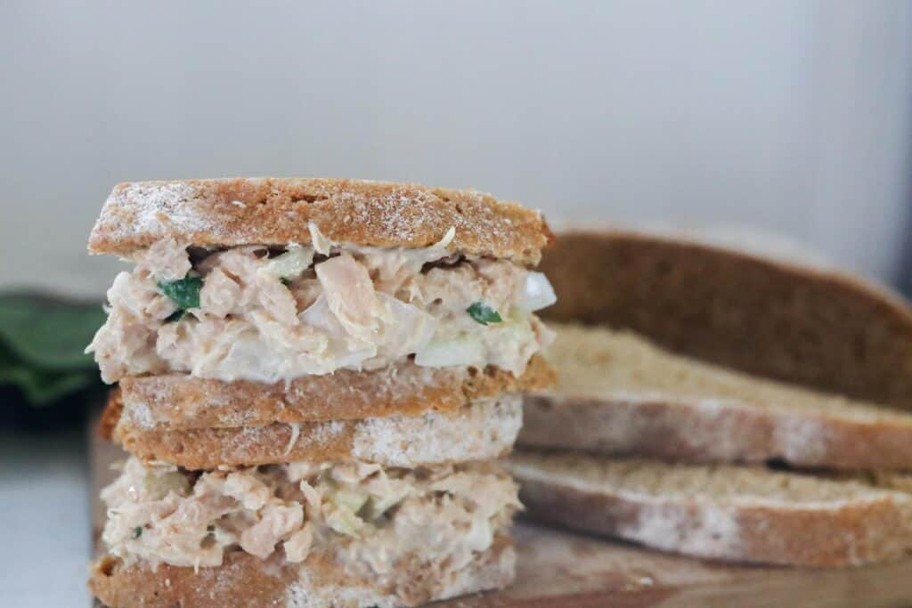 two tuna salad sandwiches stacked up with bread to the right
