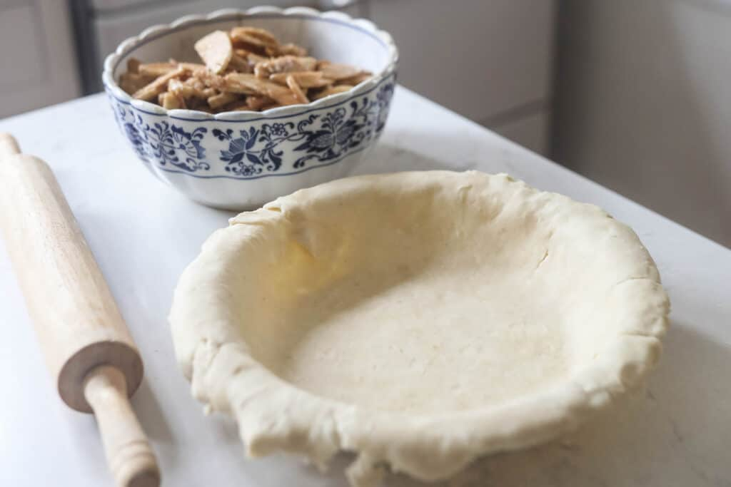 pie crust in a pie dish with sliced spiced apples in a bowl in the background