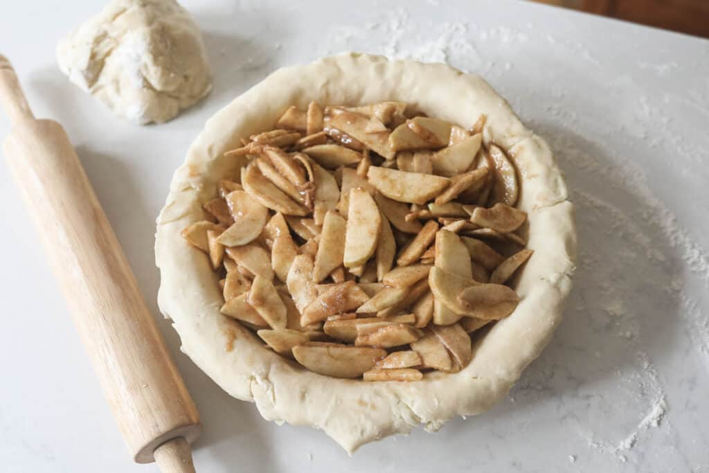 spiced and sweetened sliced apples in a unbaked sourdough pie crust ready for the oven