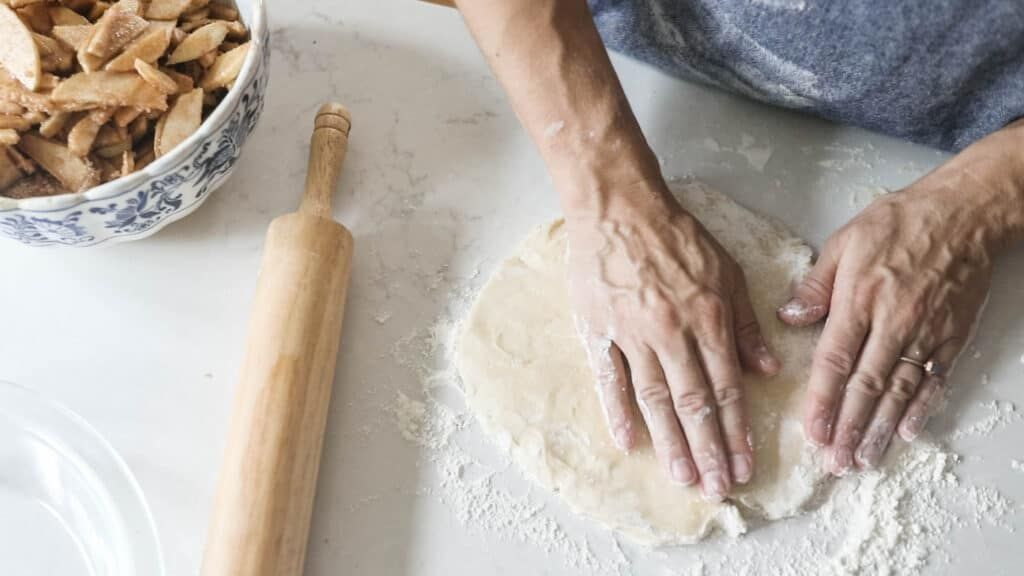 hands patting down pie crust on a floured countertop