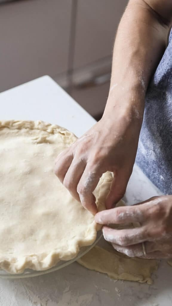 women crimping the edges of an apple pie with sourdough crust